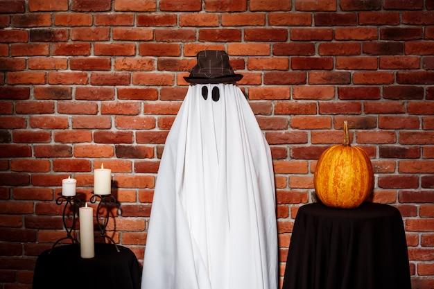 Призрак в шляпе, позирует над кирпичной стеной. halloween party. Бесплатные Фотографии