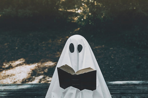 Ghost reading opened book in park Free Photo