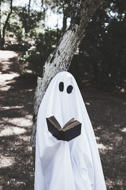 Ghoststanding at tree and reading book Free Photo