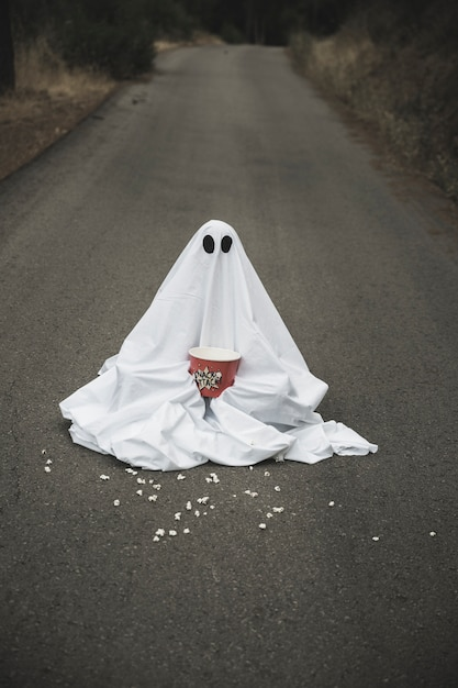 Ghost with popcorn box sitting on road with spreading grains Free Photo