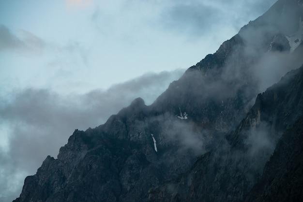Призрачные гигантские скалы с деревьями в густом тумане. таинственная огромная гора со снегом в тумане. раннее утро в горах. непроницаемый туман. темный атмосферный жуткий пейзаж. спокойная мистическая атмосфера. Premium Фотографии