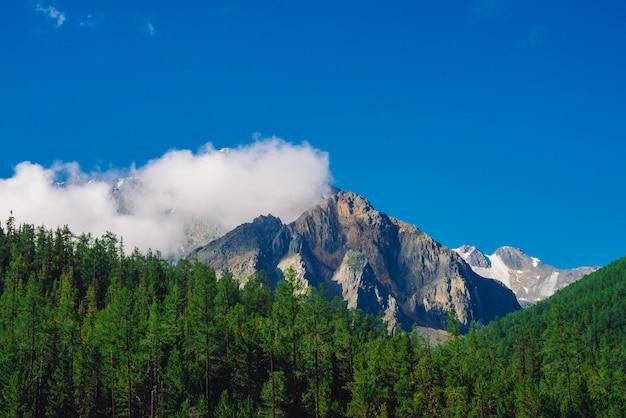 晴れた日の巨大な岩。針葉樹林に覆われた丘の後ろに雪で岩が多い尾根。青空の下で巨大な雪に覆われた山脈の上の雲。雄大な自然の大気の高地の風景。 Premium写真