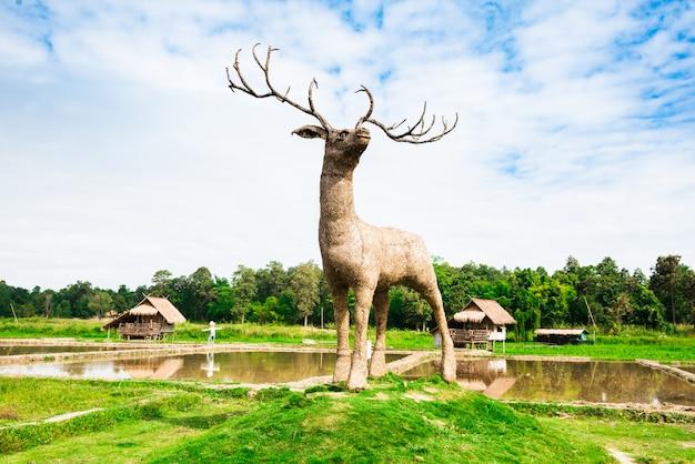 Гигантские деревянные олени на рисовом поле Premium Фотографии