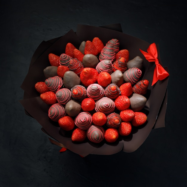 Gift bouquet collected from ripe strawberries covered with brown chocolate on a black background Premium Photo