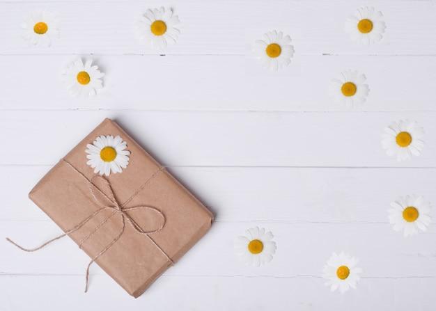 Подарочная коробка и ромашка на деревянных фоне Premium Фотографии