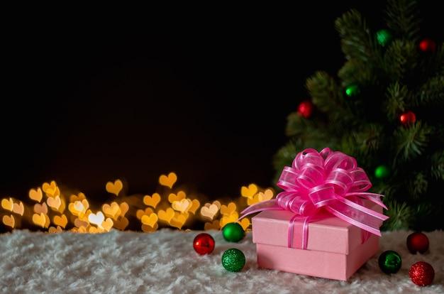 Подарочная коробка и украшения с елкой и любовью формируют фон огней боке. Premium Фотографии