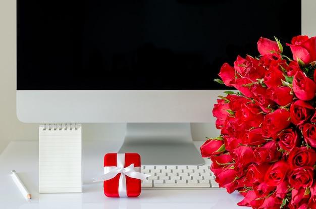 Подарочная коробка и букет красных роз на рабочем столе для концепции дня святого валентина. Premium Фотографии