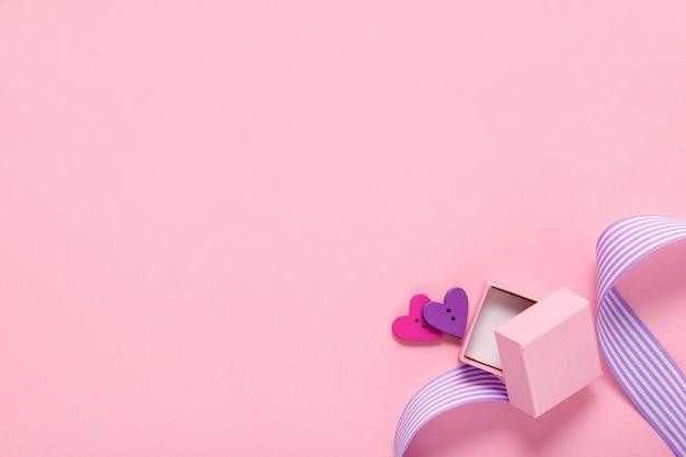 Подарочная коробка и два сердца на розовом Premium Фотографии