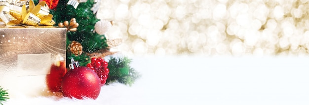 Gift box and ball decoration under christmas tree on white fir with bokeh background Premium Photo
