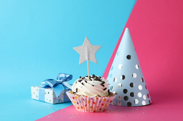 Gift box, birthday hat and cupcake on two tone background, space for text Premium Photo