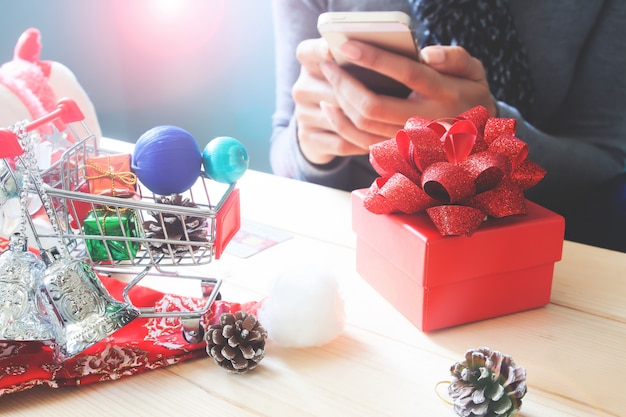 Gift box and christmas ornament on table with woman using mobile phone Premium Photo