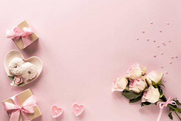 Gift box or gift box and flowers on pink table top view. Premium Photo