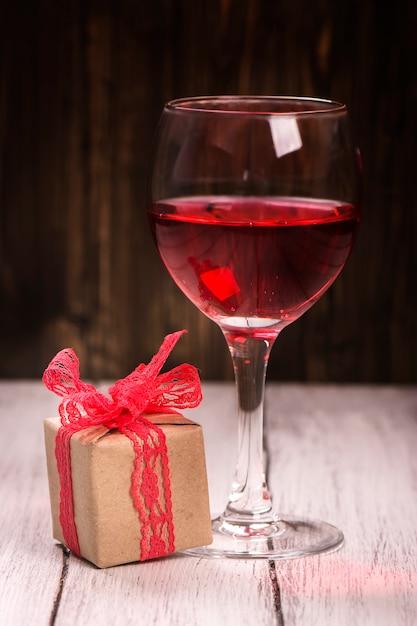 Gift box and glass of pink wine Premium Photo