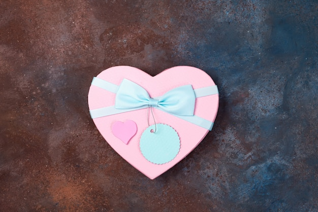 Gift box heart with a ribbon on stone background, flat lay. Premium Photo