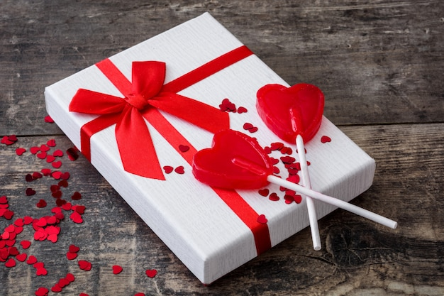 Gift box and lollipops on wooden background valentines concept Premium Photo