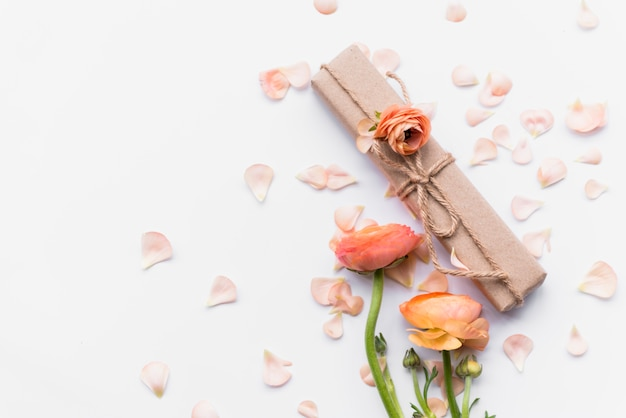 Gift box near flowers on petals Free Photo