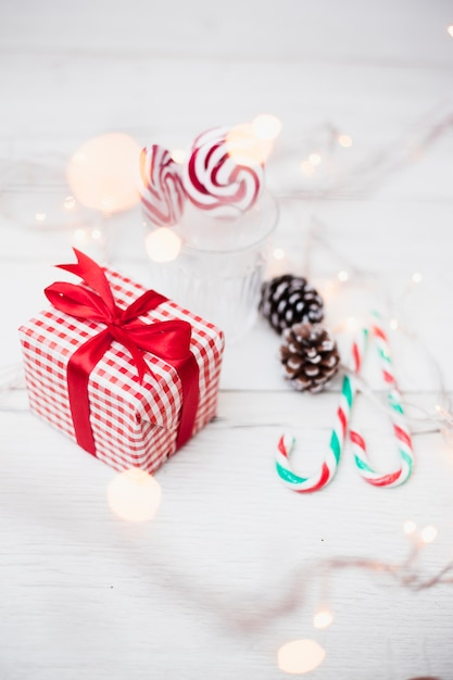 Gift box near glass with lollipops, candy canes and illuminated fairy lights Free Photo