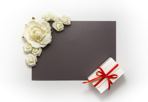 Gift box present decorations flatlay. gift red ribbon white flowers top view. Premium Photo