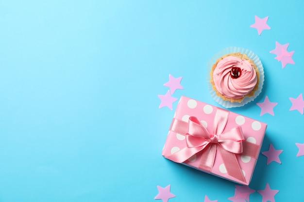 Подарочная коробка, звезды и кекс на синем фоне, место для текста Premium Фотографии