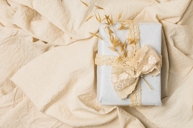 Gift box tied with designer lace over creased bed sheet Free Photo