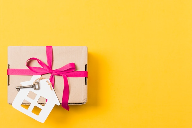 Gift box tied with key and house model over bright yellow background Free Photo