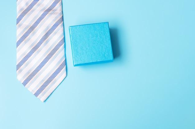 青い背景にネクタイとギフトボックス、父親のための準備。世界国際男性デーと父の日のコンセプト Premium写真