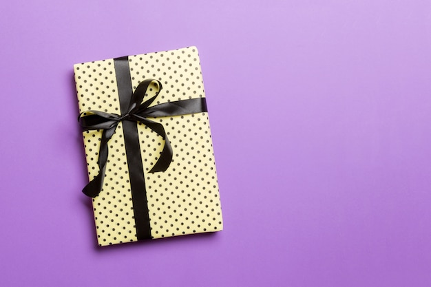 Gift box with black bow for christmas or new year day on purple Premium Photo