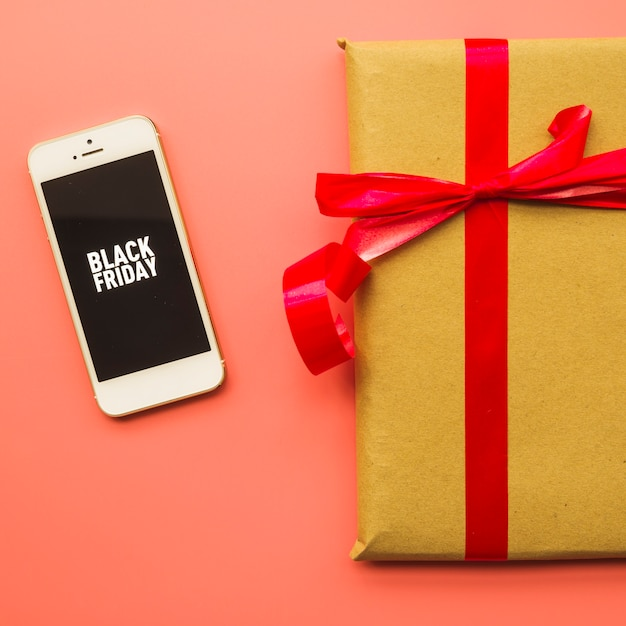 Gift box with black friday inscription on phone Free Photo