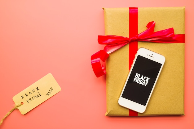 Gift box with black friday inscription on smartphone Free Photo