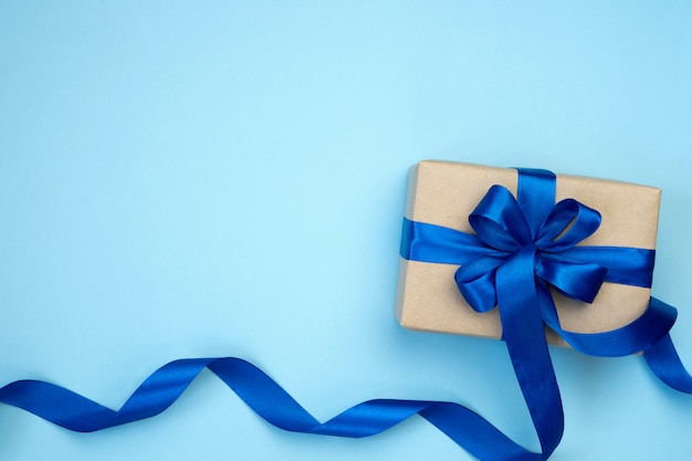 Gift box with blue ribbon bow isolated on blue background. Premium Photo