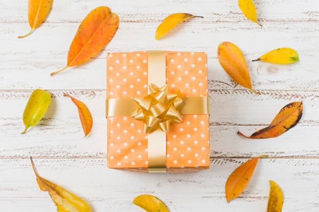 Gift box with bow and autumn leaves over wooden surface Free Photo