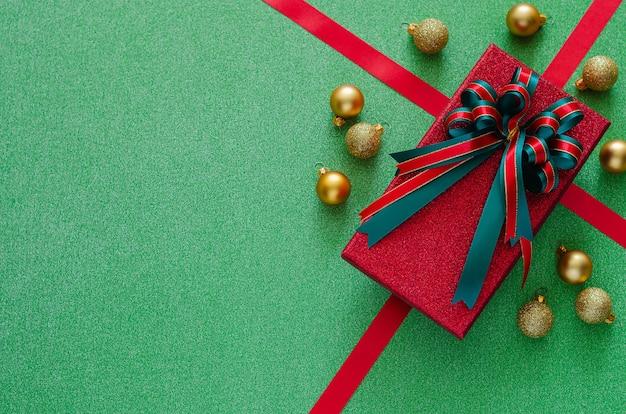 Подарочная коробка с бантовой лентой и рождественскими украшениями безделушек на зеленом. Premium Фотографии