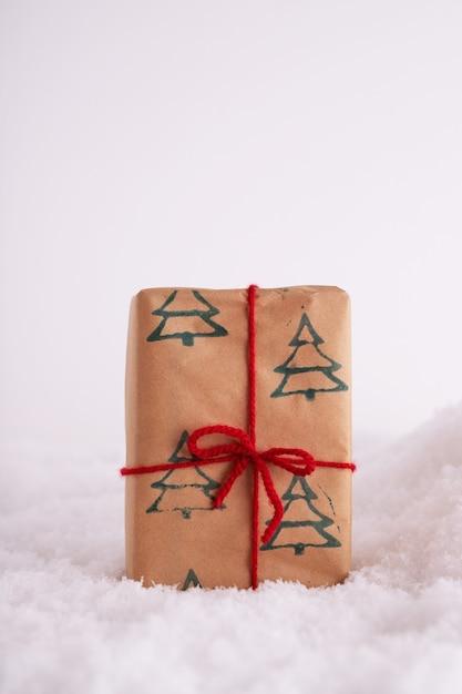 크리스마스 트리 패턴과 눈에 빨간 리본 선물 상자 무료 사진