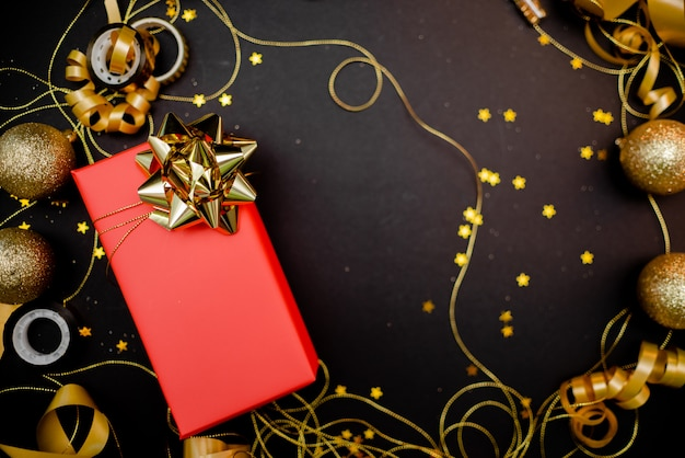 Gift box with golden bow on black background with decoration and sparkles Premium Photo