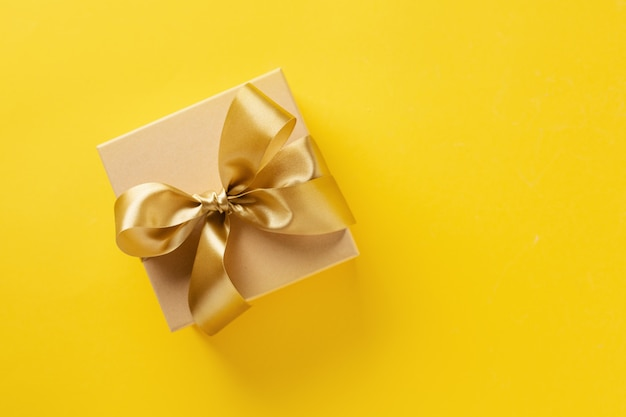 Gift box with golden ribbon on bright background Free Photo