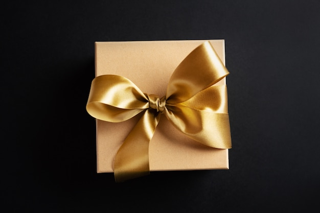 Gift box with golden ribbon on dark surface Free Photo