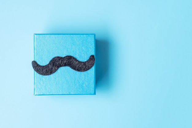 青い背景に口ひげを生やしたギフトボックス、父親のための準備。世界国際男性デーと父の日のコンセプト Premium写真