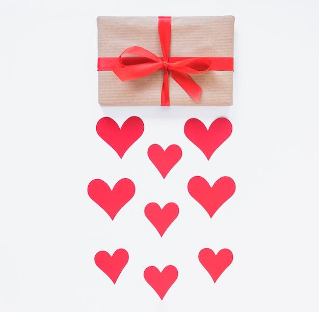 Confezione regalo con cuori rossi sul tavolo Foto Gratuite