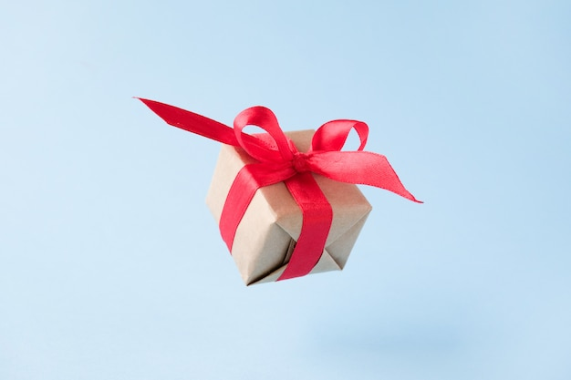Gift box with red ribbon on blue. Premium Photo