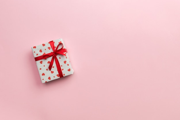 Gift box with red ribbon and heart on pink Premium Photo