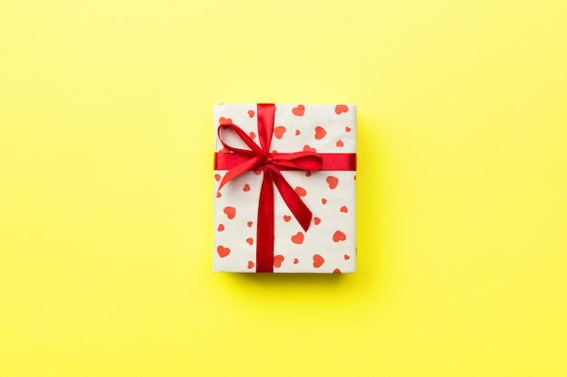 Gift box with red ribbon and heart on yellow background, top view with copy space for text Premium Photo