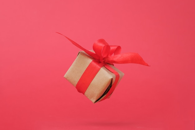 Gift box with red ribbon on red. Premium Photo