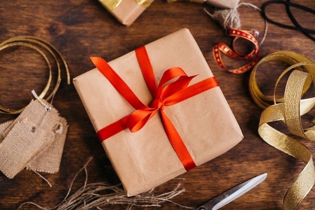 Gift box with red ribbon on table Free Photo