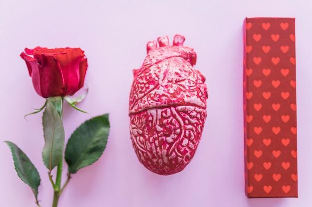 Confezione regalo con rosa rossa sul tavolo Foto Gratuite