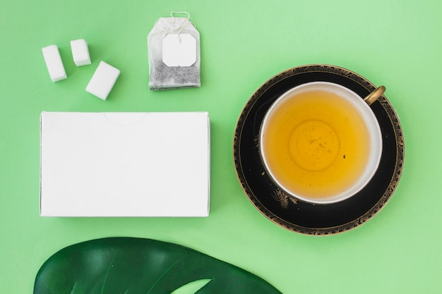 Gift box with sugar cube, tea bag, leaf and herbal tea cup on green