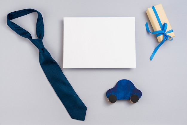 Gift box with toy car, paper and tie Free Photo