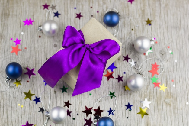 Gift box with violet satin ribbon on the wooden table Premium Photo