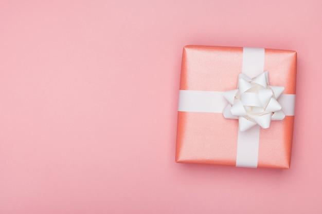 분홍색 표면에 흰 나비 선물 상자입니다. 생일 또는 기념일 인사말 카드 프리미엄 사진