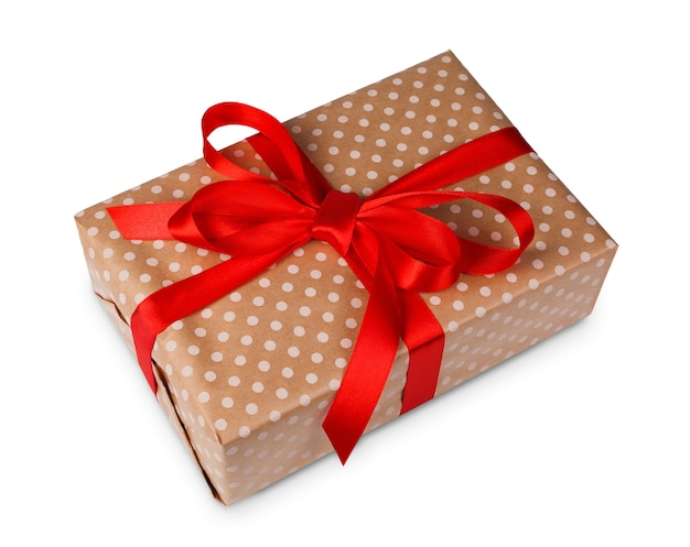 Gift box wrapped with dotted beige paper and red satin ribbon, isolated on white Premium Photo