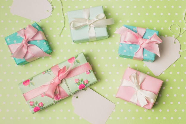 Gift boxed wrapped in design paper with white tag over green polka dot surface Free Photo